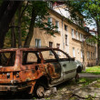 Residental house and burned-down vehicle — Stock Photo