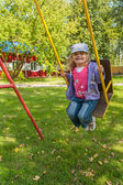 Smiling girl on swing — Stock Photo