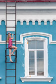 Pretty woman on fire escape stair — Stok fotoğraf