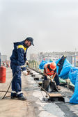 Workers make waterproofing of seams on the bridge — Stock Photo