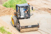 Road roller compressing sand to highway — Stock Photo