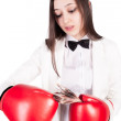 Young businesswoman in boxing gloves with cash — Stock Photo #45805975