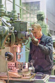 Worker drills bores on detail by driller — Stock Photo