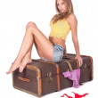 Pretty woman sitting on old suitcase — Stock Photo