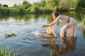 Attractive girl lowers wreath in water — Stock Photo