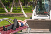 The loader driver sleeps on bench — Stock Photo