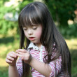 Portrait of beautiful young girl with flower in the park - Stock Photo