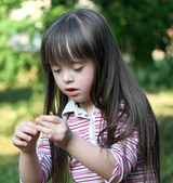 Portrait of beautiful young girl with flower in the park — Stock Photo