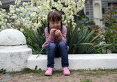 Beautiful young girl siting on flowers background. — Stock Photo