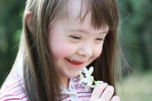 Portrait of beautiful young girl with flowers in the park — Foto Stock