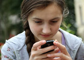 Girl playing on mobile phone — Stock Photo