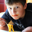 Funny boy eating spaghetti. — Stock Photo #16241417