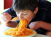 Funny boy eating spaghetti. — Стоковое фото