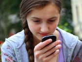 Girl with a mobile phone reads the message — Stockfoto