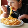 Stock Photo: Funny boy eating spaghetti.