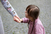 Girl holding arm of the mother on a walk — Stock Photo
