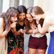 Beautiful student girls looking message on mobile phone - Stok fotoraf