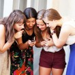 Beautiful student girls looking message on mobile phone - Stock fotografie