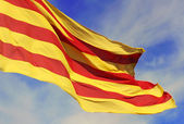 Waving flag of the Catalunya (Catalonia) on background of the blue sky. — Stock Photo