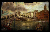 A view of the canal with Rialto bridge, boats and buildings in Venice on vintage old paper isolated on black — Stock Photo