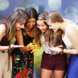 Stock Photo: Beautiful student girls looking message on mobile phone
