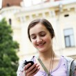 Girl listening music on mobile phone in the city — Stock Photo