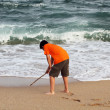 Boy draws with a stick on the sand at the beach — Stock Photo
