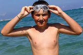 Cute boy in swimming goggles on the sea. — Stock Photo