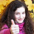Portrait of beautiful young girl giving thumbs up on background of yellow leaves — Zdjęcie stockowe #28439385