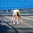 Athletic teenage girl in start position on track . — Stockfoto