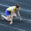 Athletic teenage girl in start position on track . — Stok fotoğraf