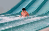 Happy boy falling into water in the aquapark — Stock Photo