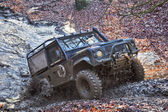 Land Rover exiting bombhole — Stock Photo
