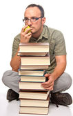 Young man sitting next to pile of books — Stock Photo