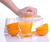 Hand squeezing orange for juice — Stock Photo