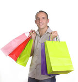 Smiling man with several shopping bags — Stock Photo