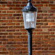 Black Lamp against Brick Background — Stock Photo
