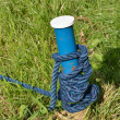 Foto Stock: Blue mooring post with rope