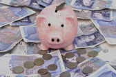 Piggy bank over notes and coins — Stock Photo