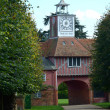 Gatehouse and clock through trees — Stock Photo