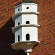 White Dovecote on red brick wall — Stock Photo