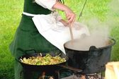 Medieval woman stirring pot — Stockfoto