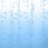 Blauwe water druppels op glas — Stockfoto