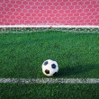 Stock Photo: Soccer ball on green grass in goal net