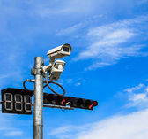 Surveillance camera and traffic light against blue sky — Stock Photo