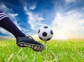 Foot kicking soccer ball on golf tee — Stock Photo