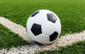 Football on green grass field conner — Stock Photo