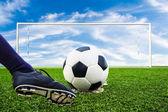 Foot kicking soccer ball — Stock Photo