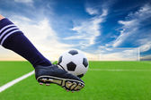 Foot kicking soccer ball — Stock Photo