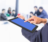 Business man hand touching tablet PC with business people backgr — Stock Photo